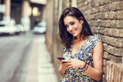 Smiling young woman using her smart phone outdoors.