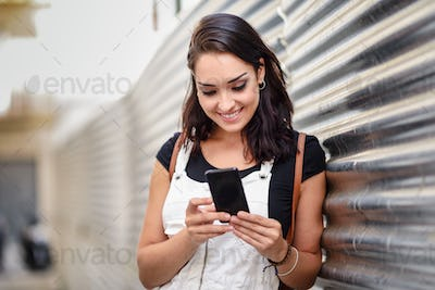 Smiling girl using with her smart phone outdoors.