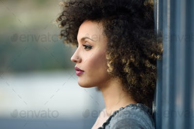 Young black woman with afro hairstyle smiling in urban backgroun