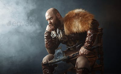 Thoughtful viking with axe sitting on chair