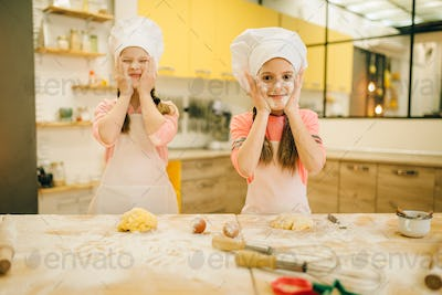 Little girls chefs smears their faces with flour