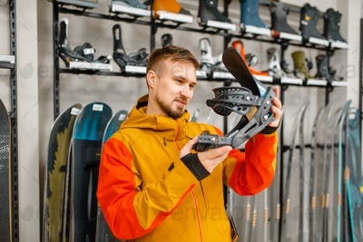 Man choosing ski boot fastening in sports shop