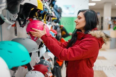 Couple choosing helmets, shopping in sports shop
