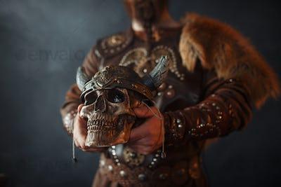 Viking holds human skull in helmet