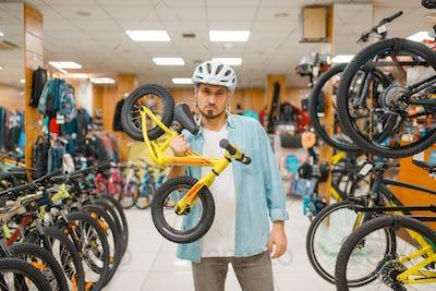 Man in helmet holds children's bicycle, sport shop