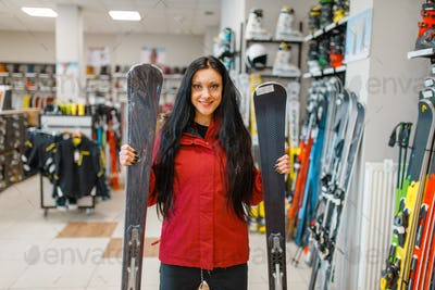 Woman at showcase holding downhill ski in hands