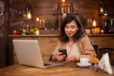 Portrait of a beautiful woman sitting in a coffee shop texting on her phone