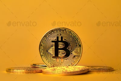 Closeup of standing gold bitcoin on yellow backgound