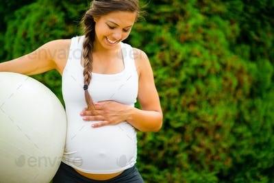 Pregnant Woman Touching Abdomen While Holding Fitness Ball In Park