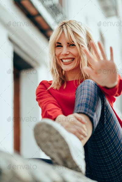 Happy blond woman sitting outdoors putting her hand near the cam