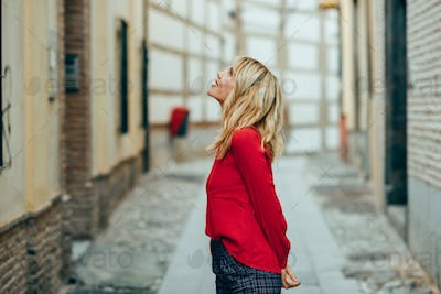 Happy young blond woman walking down the street.