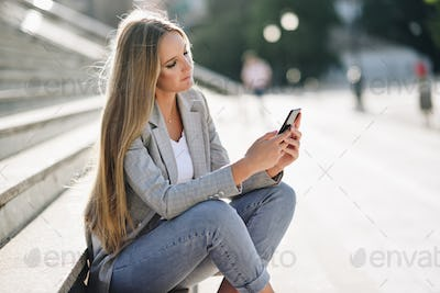 Beautiful young blonde woman looking at her smartphone.