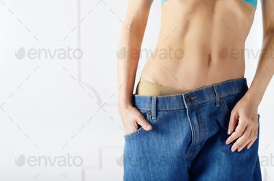 Caucasian female model in blue jeans showing her flat stomach. W