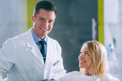 Pretty Young Woman with Beautiful White Teeth at Appointment in