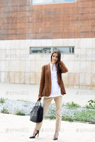 Young businesswoman standing outside of office building with bri
