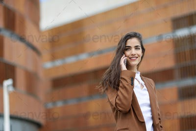 Young businesswoman talking with a smartphone in urban backgroun