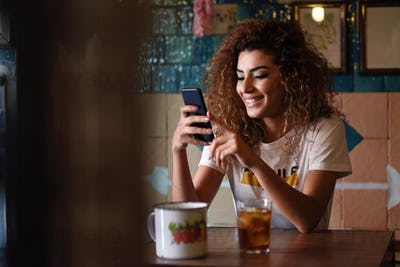 Arabic smiling woman in a beautiful bar looking at her smartphon