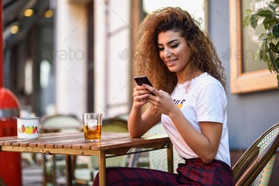 Arab woman in an urban bar at her smartphone.