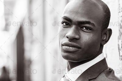 Handsome black man wearing suit in urban background