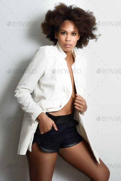 Young black woman afro hairstyle possing near a white wall
