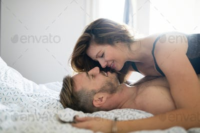 Attractive sexy woman with her partner in bedroom