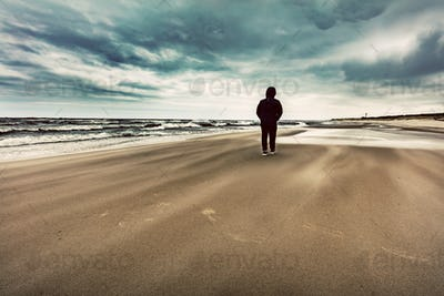Man walking alone on the beach on windy stormy day.