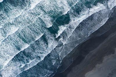 Aerial drone view of ocean waves splashing black sand beach, Iceland