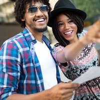 Happy young black couple of travellers holding map in hands