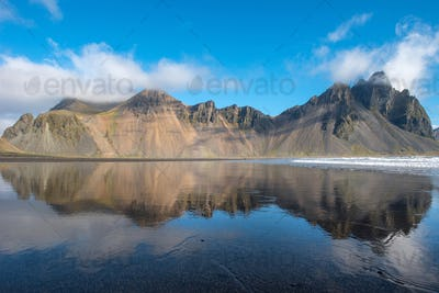 Reflection of Vestrahorn mountain in the waters of the Atlantic ocean. Stokksnes, Hofn, Iceland