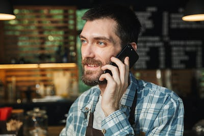 Portrait of happy barista guy talking on cellphone in street caf