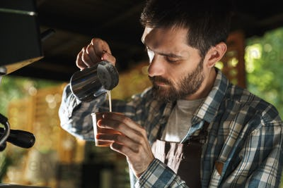 Image of masculine barista man making coffee while working in ca