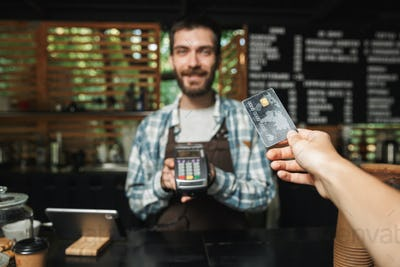 Portrait of handsome barista man taking credit card from custome