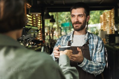 Portrait of unshaved barista man smiling while working in street