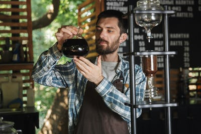 Image of satisfied barista boy making coffee while working in ca