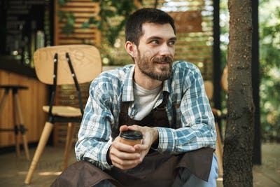 Photo of bearded waiter man sitting on wooden floor while workin
