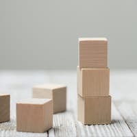 Three wooden toy cubes on grey wooden background