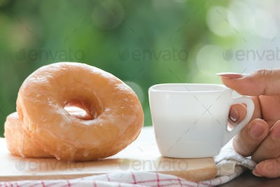 Cup of black coffee with sugar donuts