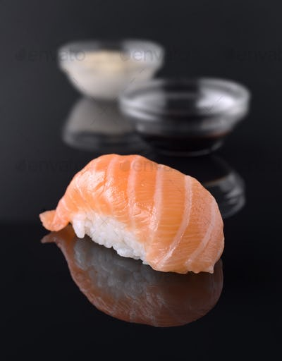 sushi with sauce bowl on black mirror background