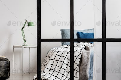 Closeup of stylish bright bedroom interior with wall divider
