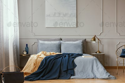 Dark blue and orange blankets on comfortable double bed in grey stylish bedroom
