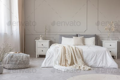 Chic feminine bedroom interior in trendy apartment, copy space on empty wall