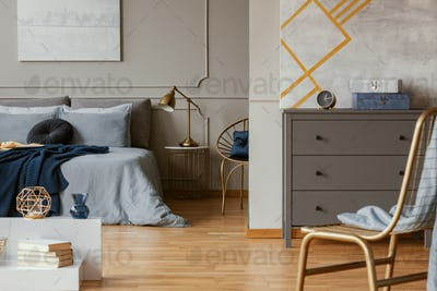 Trendy bedroom interior with grey commode and golden chair