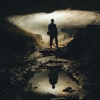 man exploring dark cave underground tunnel