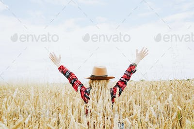 Young cowgirl in a field of cereals