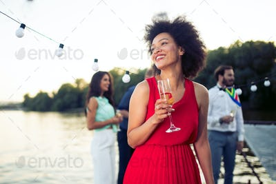 Attractive young afro woman with a drink on a terrace of a bar