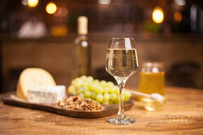 Photo of a sparkling white wine on a rustic wooden table in a vintage pub