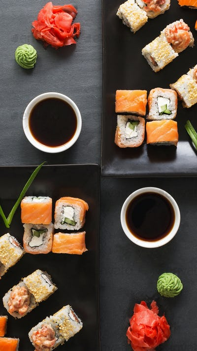 Set of rolls and sushi for two with sauce and red ginger on black