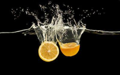 Halves of ripe orange dropped in water