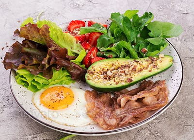 Plate with a keto diet food. Fried egg, bacon, avocado, arugula and strawberries. Keto breakfast.
