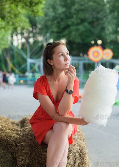young adult woman sitting on bale of hay and holding white cotton candy at amusement park